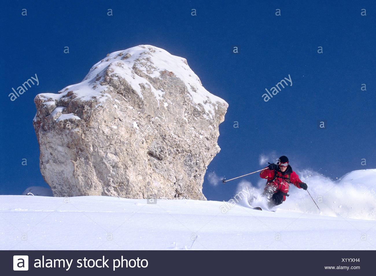 skier passing a single, almost spherical big rock, France, Rhne-Alpes, Les Arcs. - Stock Image
