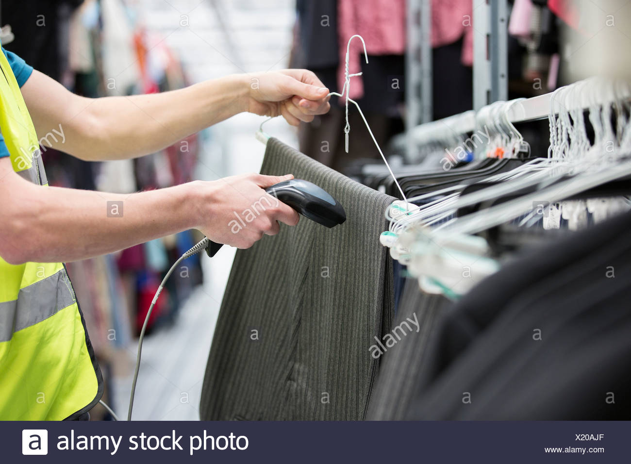 Man checking pair of trousers in warehouse - Stock Image