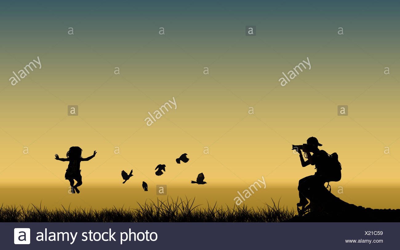 Silhouette of photographer taking picture of jumping girl and flying birds - Stock Image