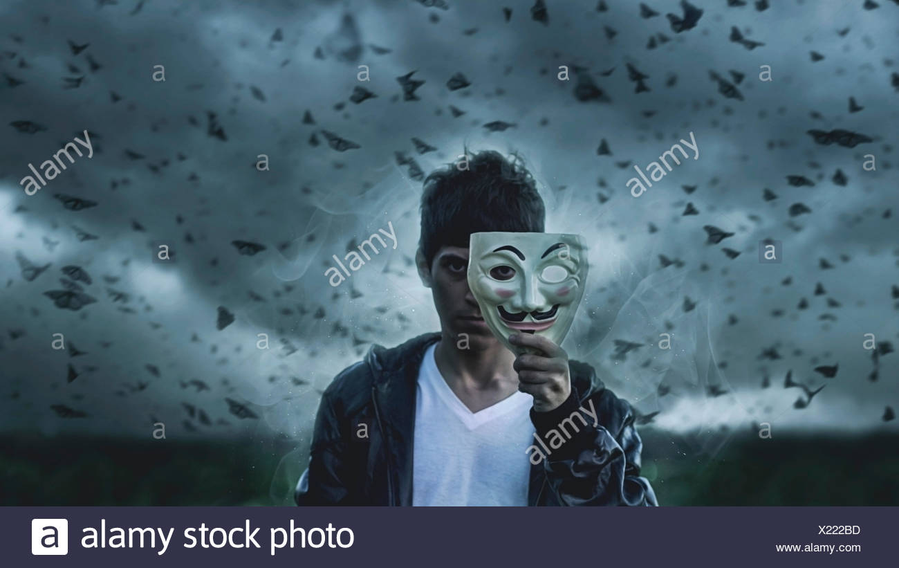 Man holding mask in front of his face with butterflies in background - Stock Image