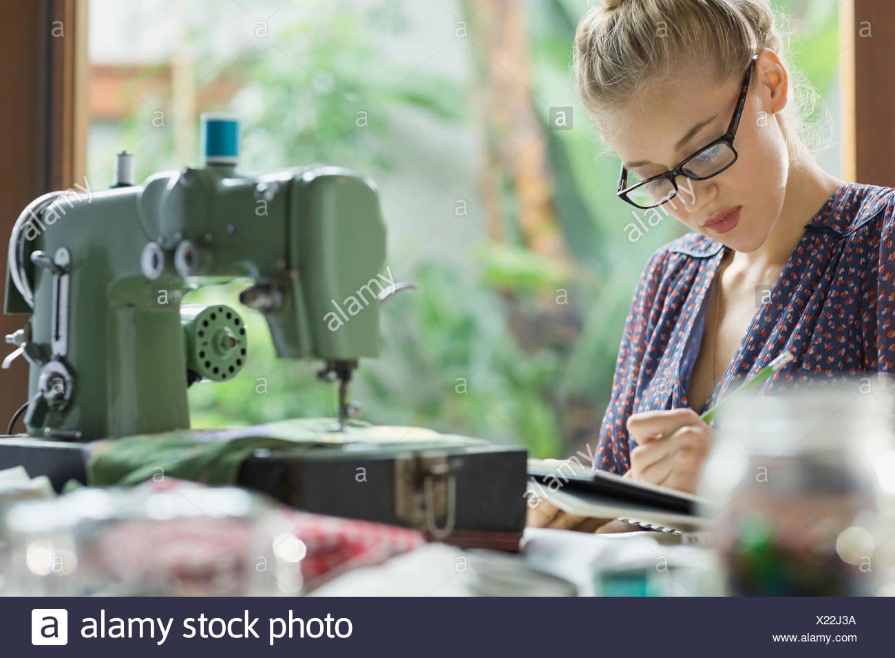 Fashion designer sketching ideas in sketchbook - Stock Image