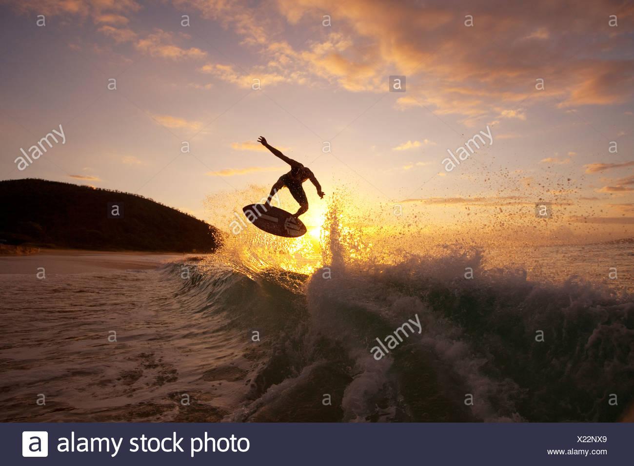 Hawaii, Maui, Makena, Skimboarder Gets Big Air Off A Wave At Sunset - Stock Image