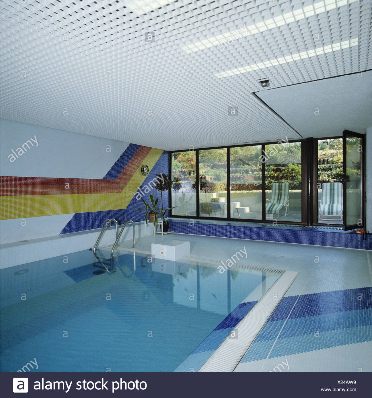 Colorful striped tiling on wall of modern indoor swimming pool with ...