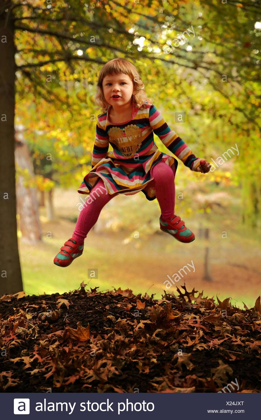 Portrait Of Cute Girl Jumping At Park - Stock Image