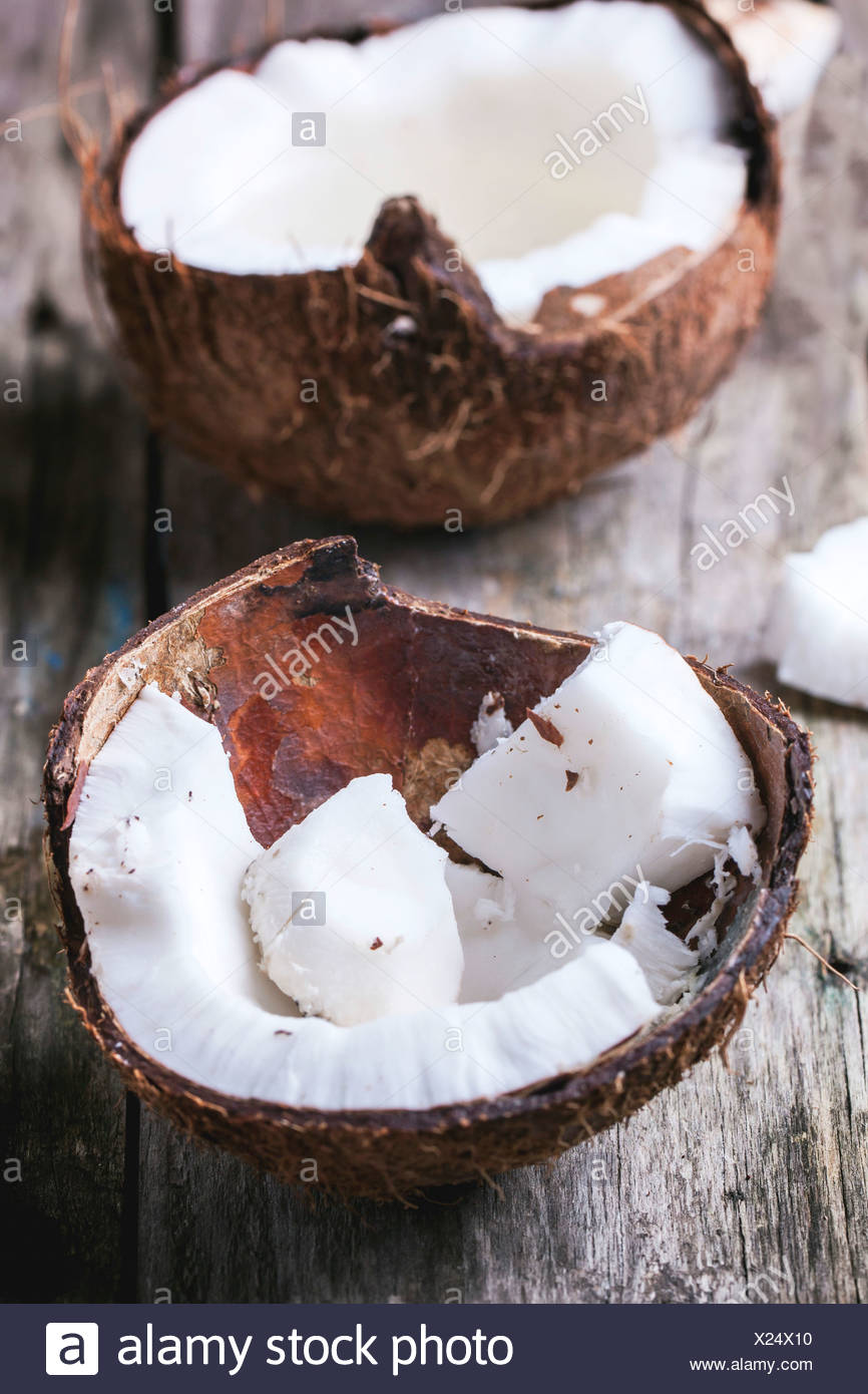 Broken coconut shell on old wooden background - Stock Image