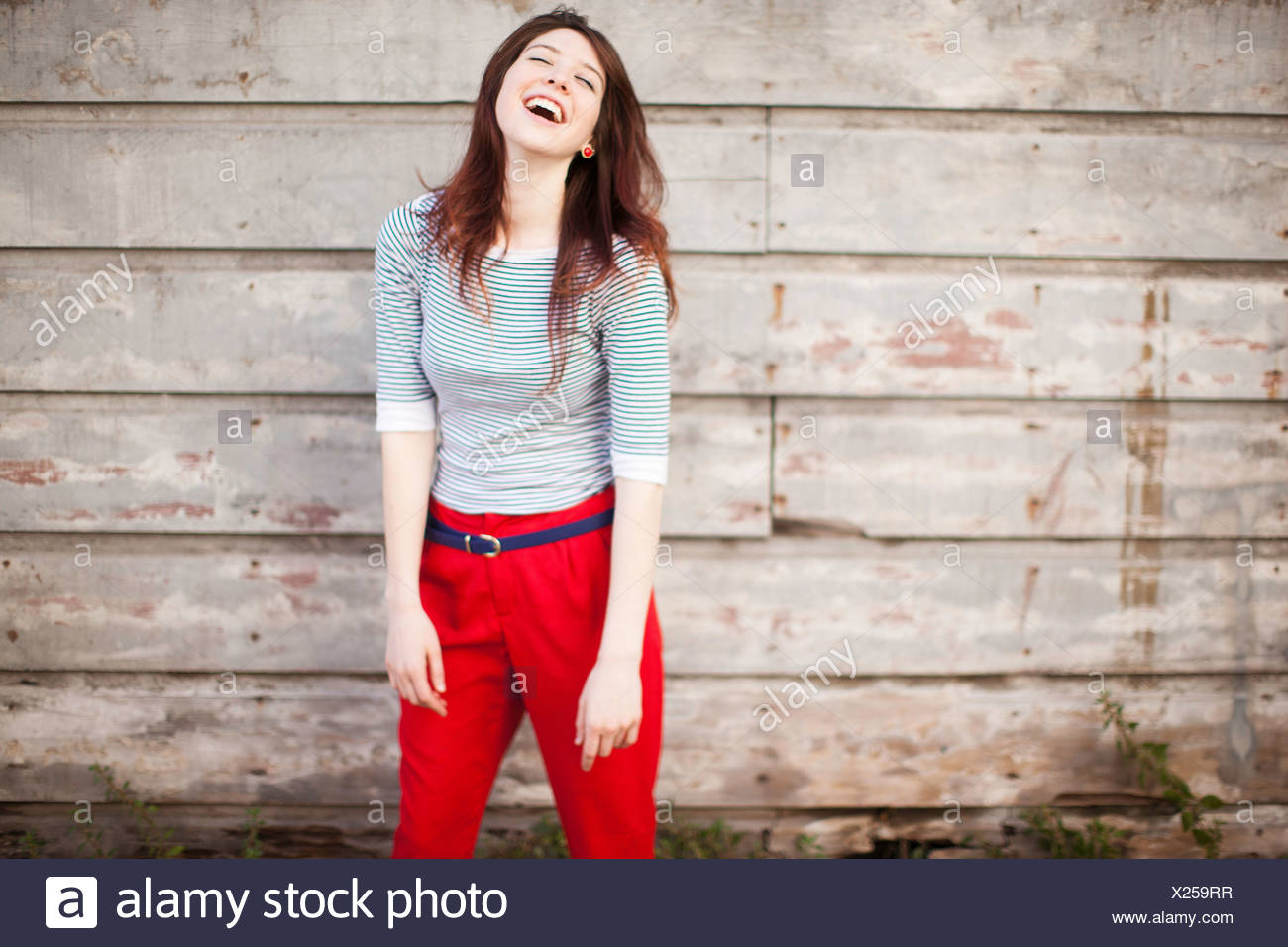 Portrait of young woman laughing - Stock Image