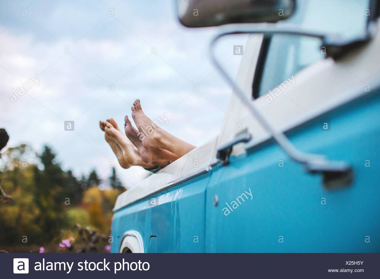 Young couple lying in back of truck, bare feet on edge of truck, focus on feet - Stock Image