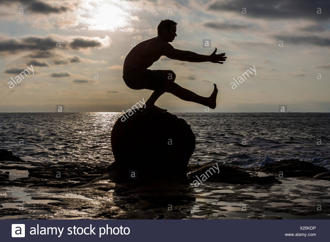 The silhouette of a shirtless male CrossFit athlete as he performs a pistol or one-legged squat on a rock in the Pacific Ocean in San Diego, California at sunset. - Stock Image