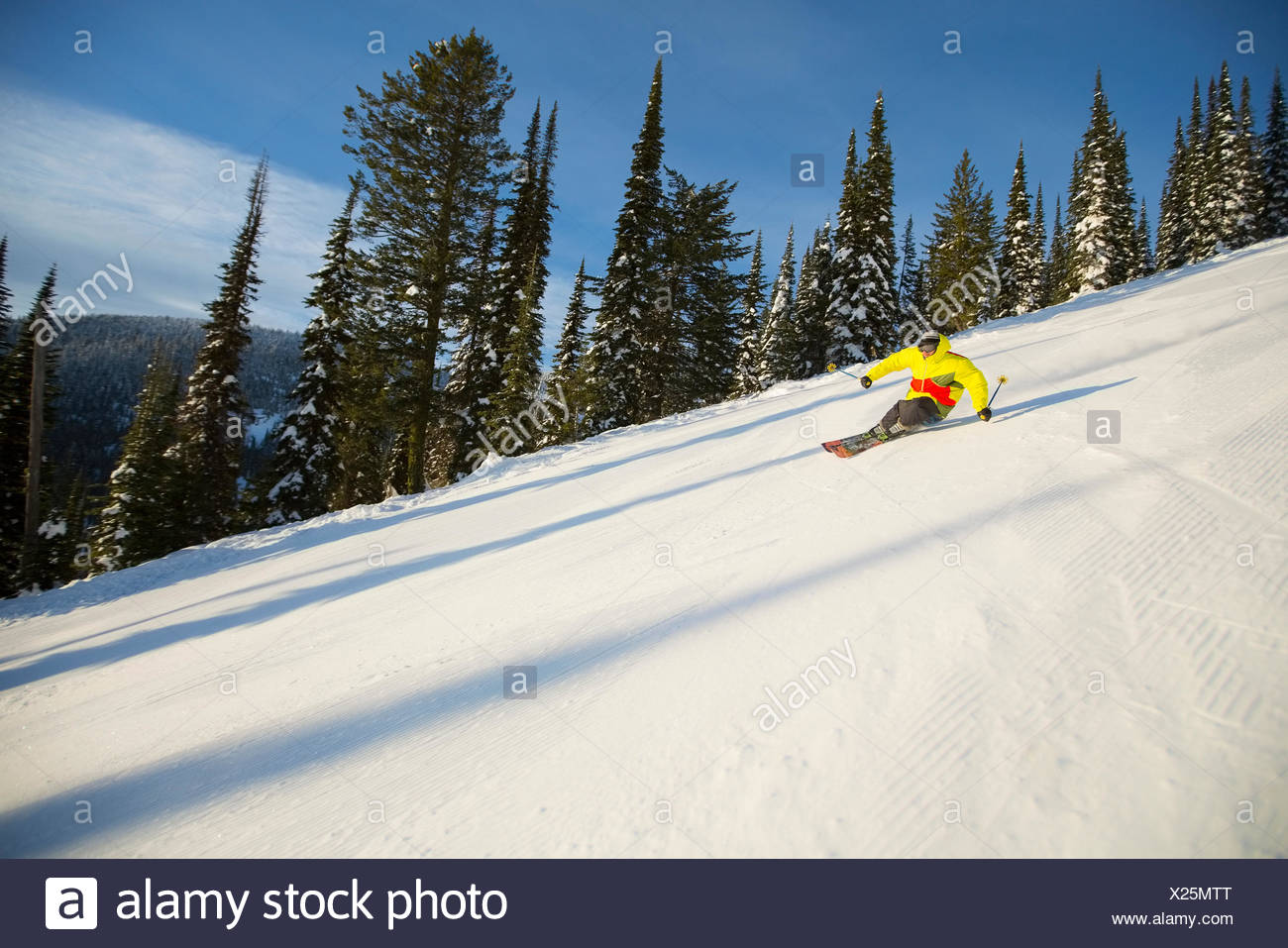Low angle view of young man on ski slope - Stock Image