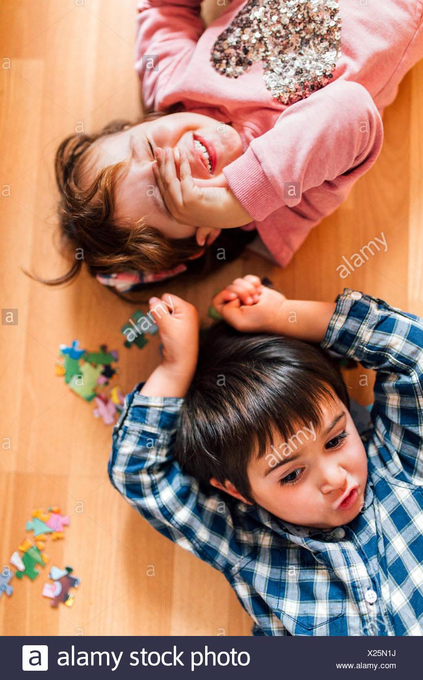 Boy and girl lying on the floor - Stock Image