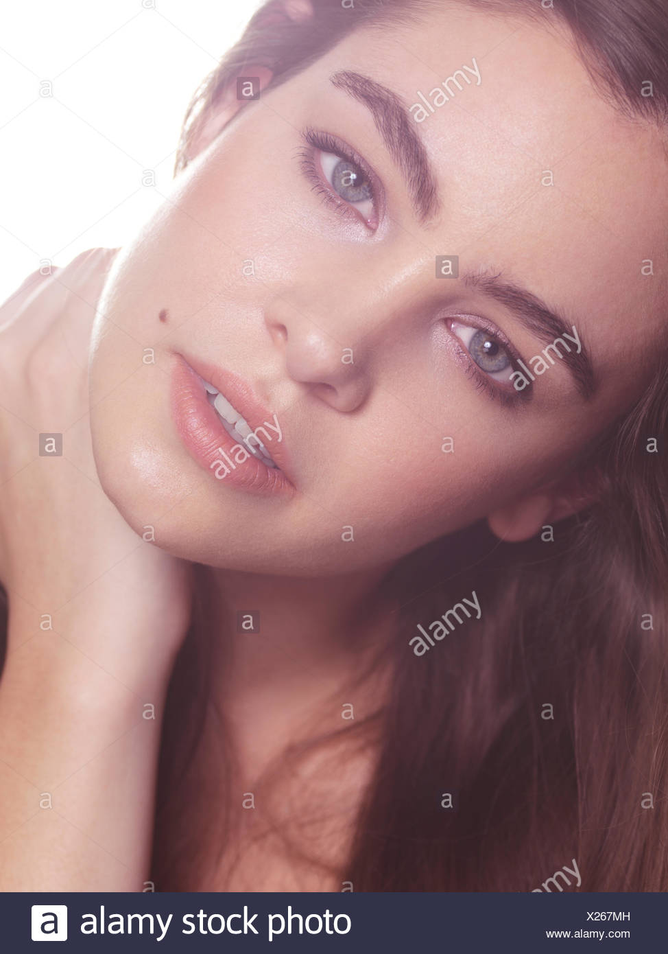 Woman With Long Hair And Bushy Eyebrows In Soft Light Stock Photo