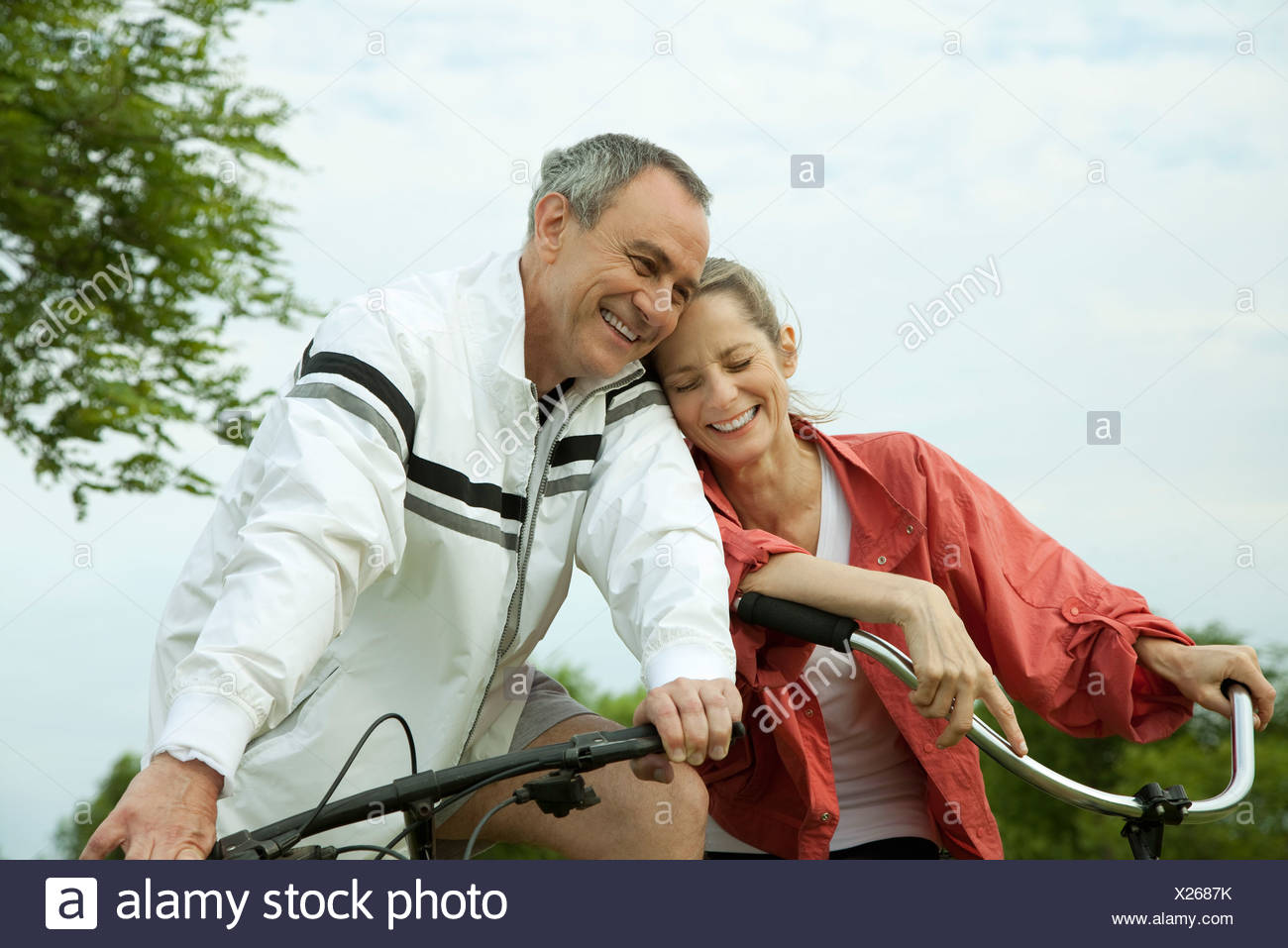 mature couple riding bikes, leaning against each other stock photo
