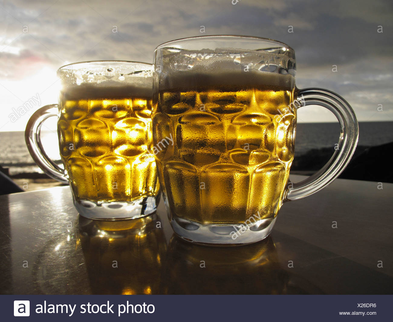 Spain, Two beer glasses on table with sea in background - Stock Image