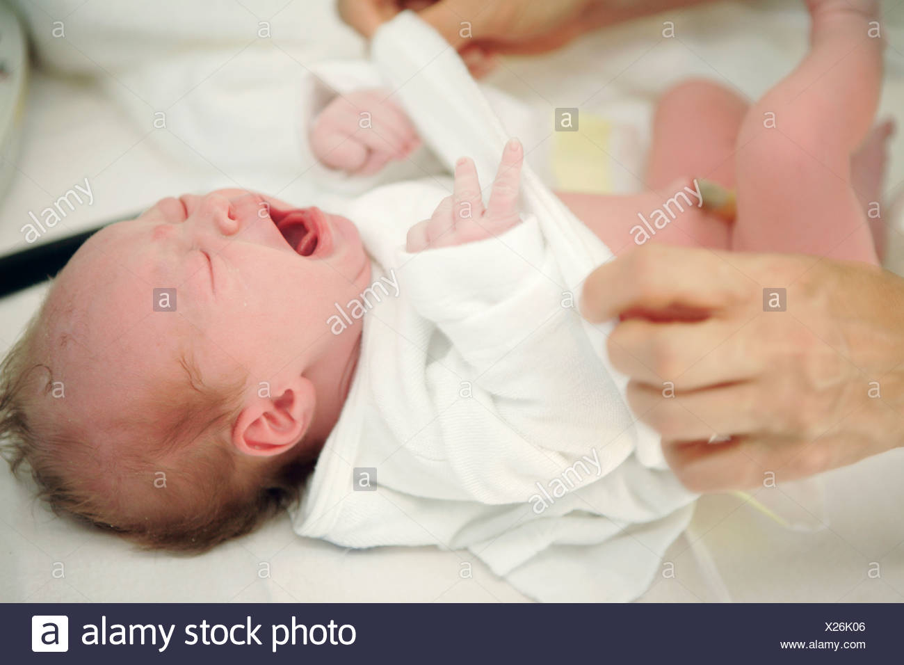 Close up of a person s hands examining a newborn baby girl - Stock Image