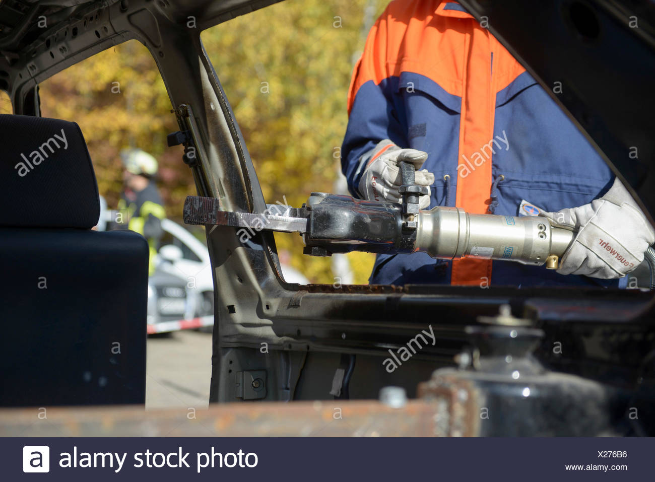 Firefighter working with hydraulic rescue equipment, final fire service drill of the young Stuttgart firefighters in autumn - Stock Image