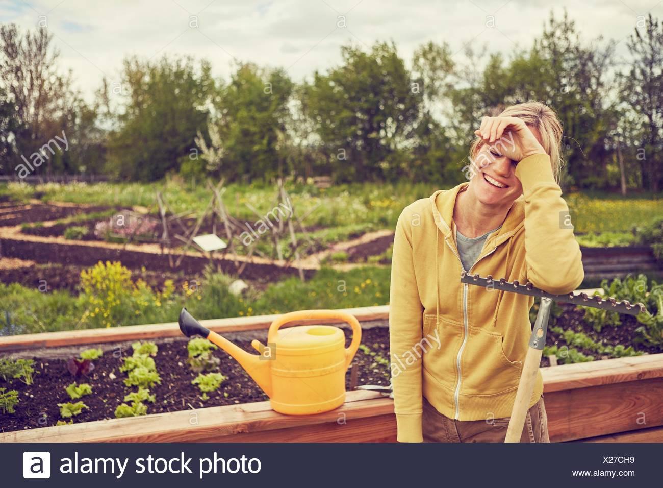 Mature woman, gardening, leaning on rake, laughing - Stock Image
