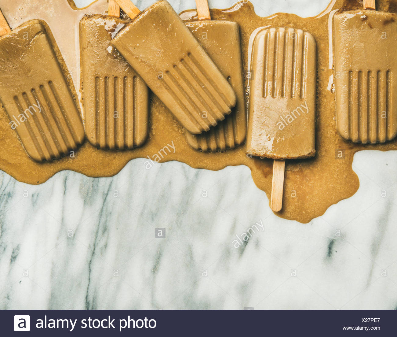 Summer healthy vegan frozen dessert. Flatlay of melting coffee latte popsicles over light grey marble background, top view, copy space, horizontal com - Stock Image