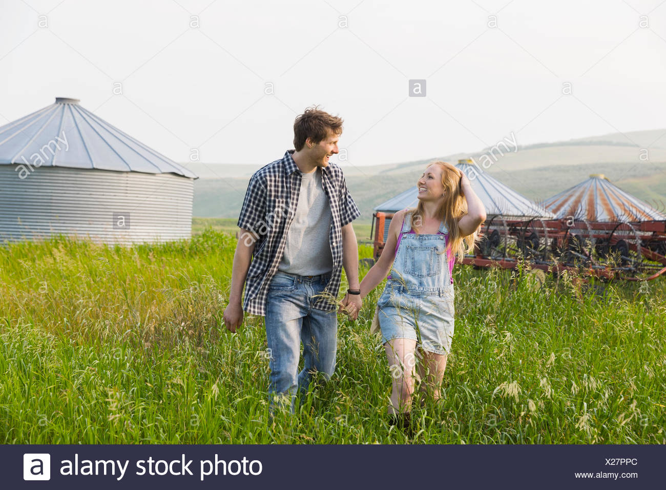 Couple holding hands and walking in rural field - Stock Image