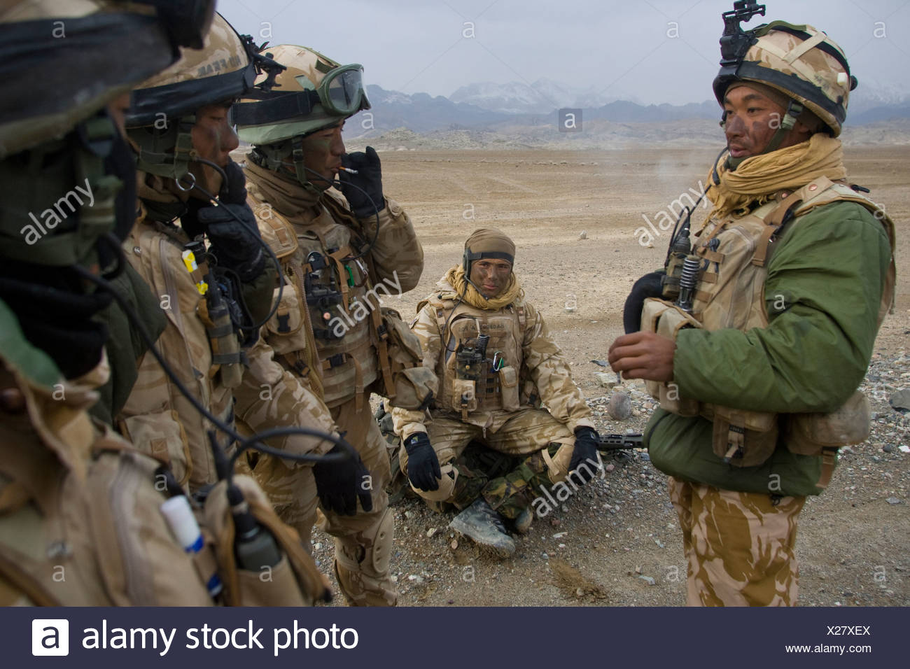 A group of Gurkha soldiers wait for a helicopter. - Stock Image