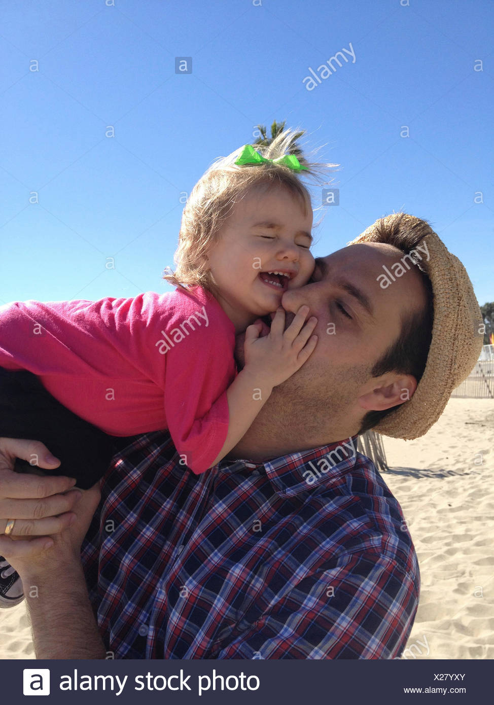 Father and daughter (18-23 months) having fun on beach - Stock Image
