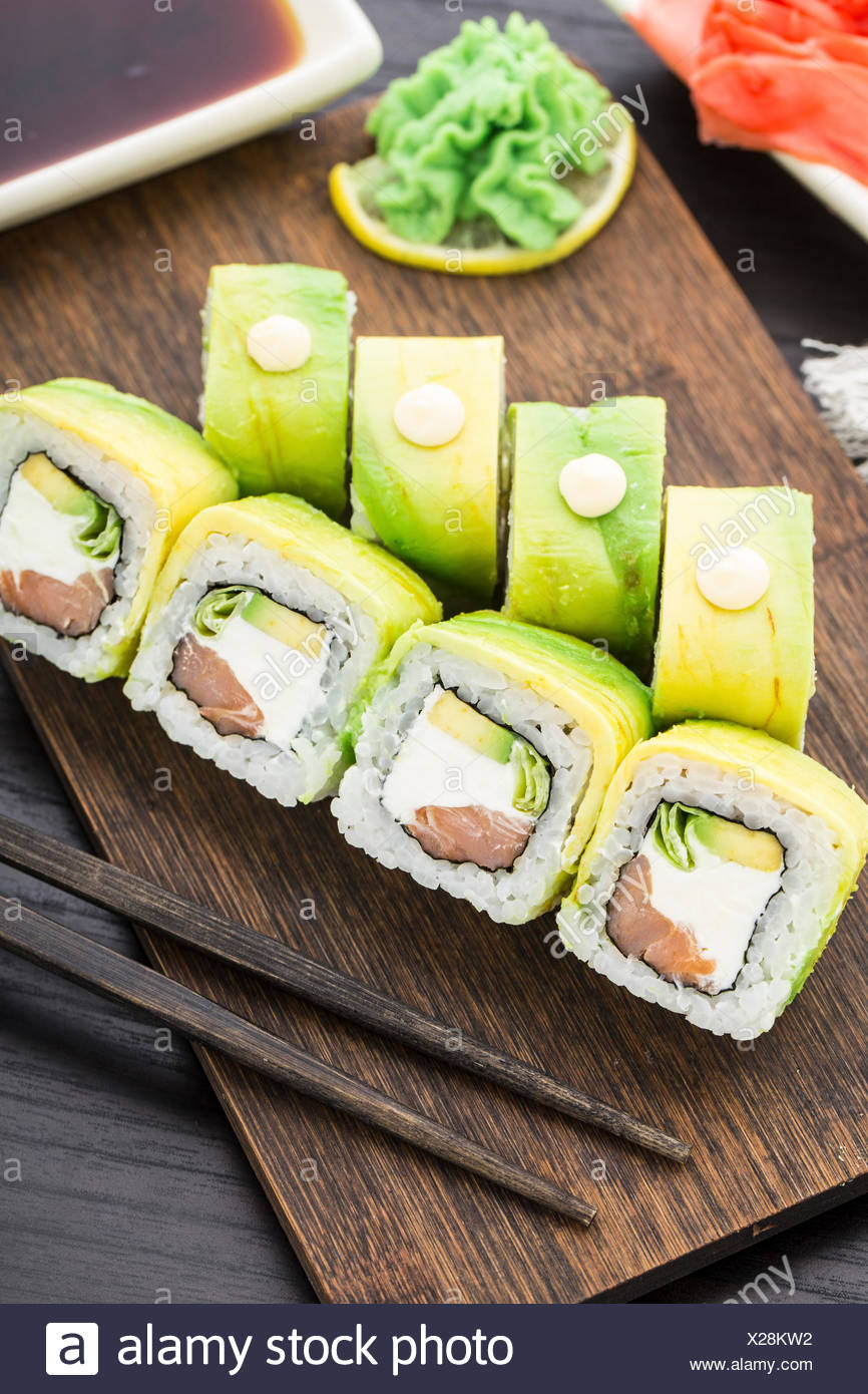 Sushi roll with salmon and lettuce wrapped by avocado - Stock Image