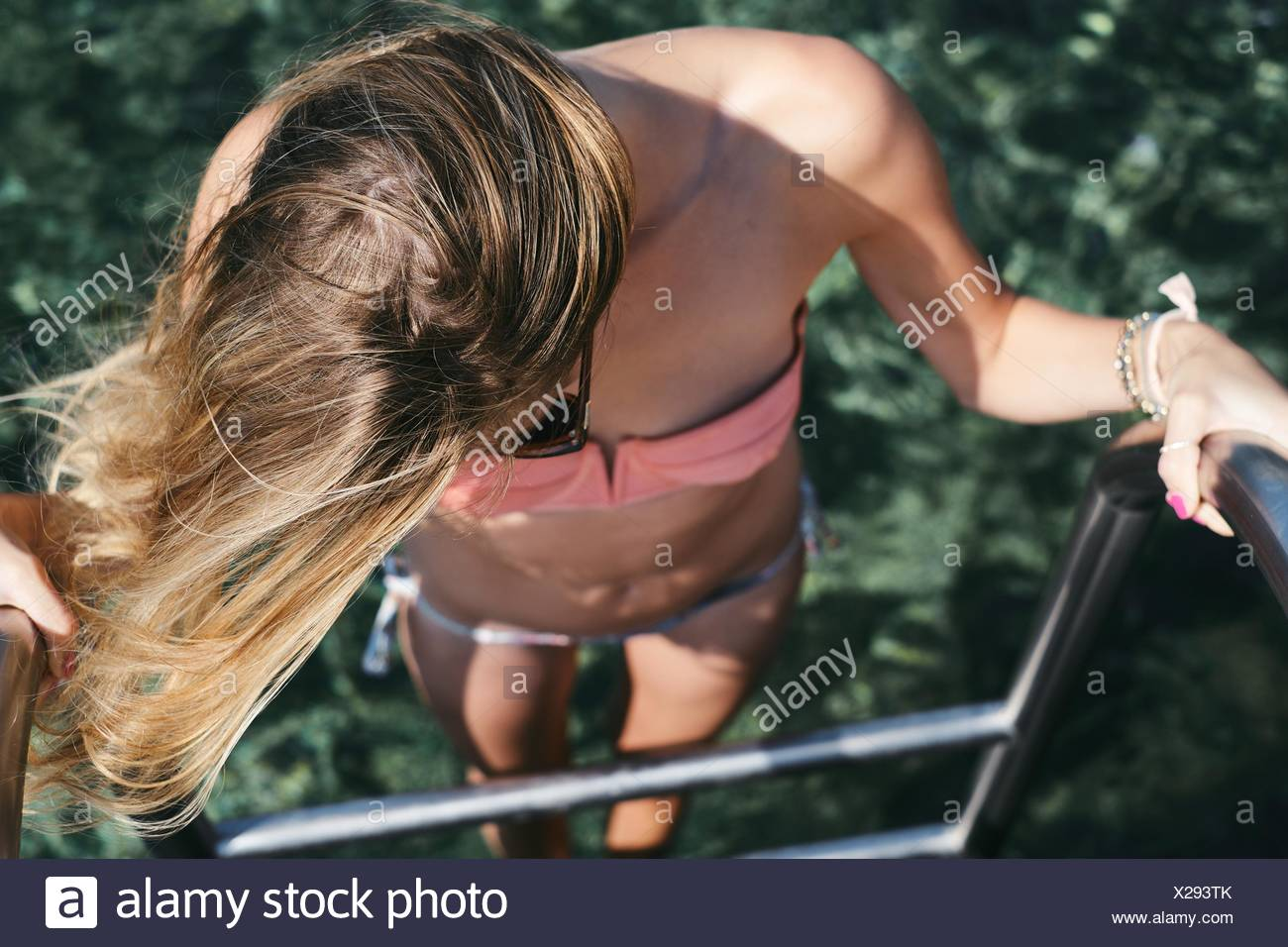 Elevated view of a woman getting into sea - Stock Image