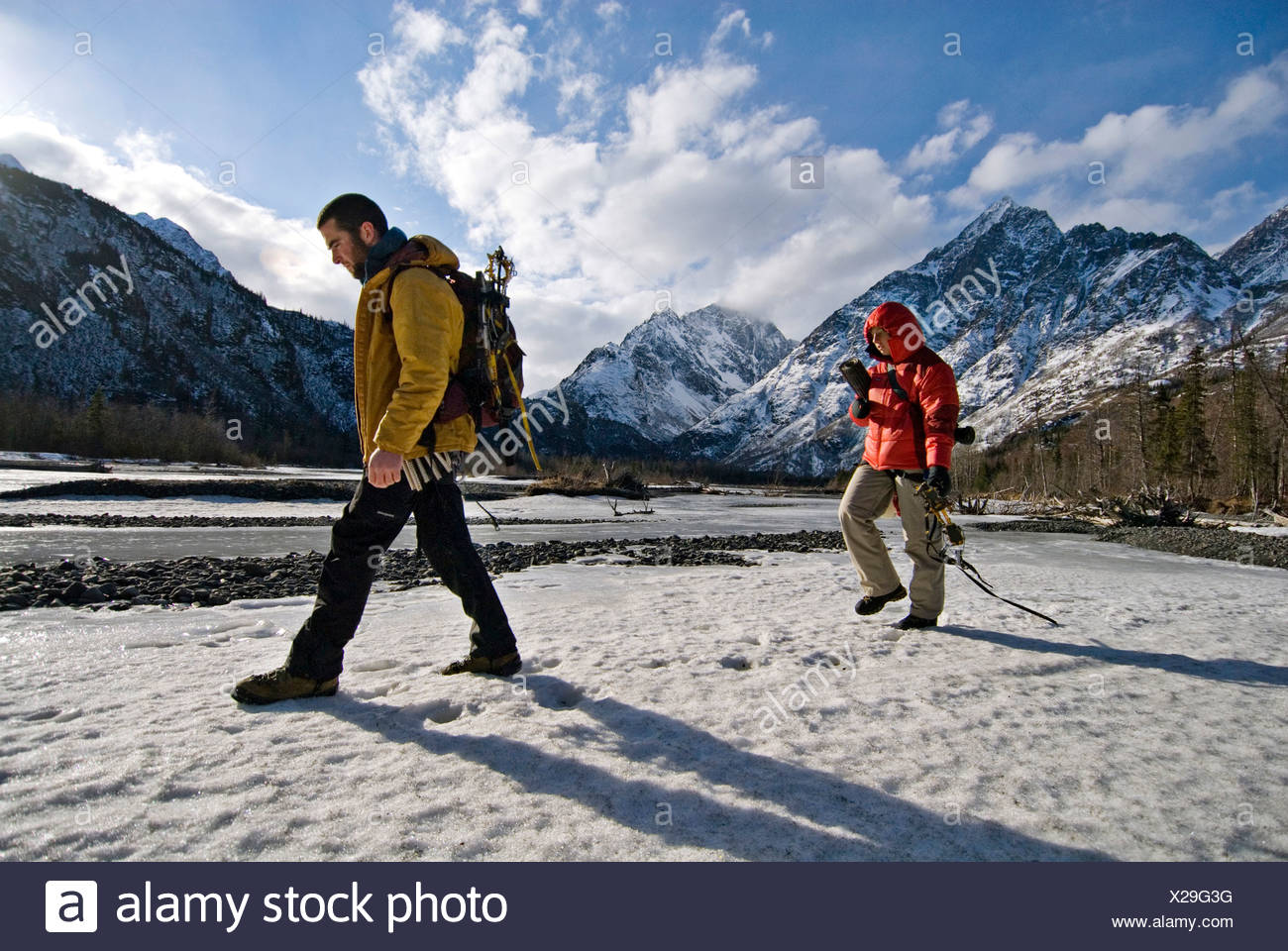 Two young ice climbers walk across a snowy river, with gear in hand, on their way to an afternoon ice climb in Echo Bend, Alaska - Stock Image