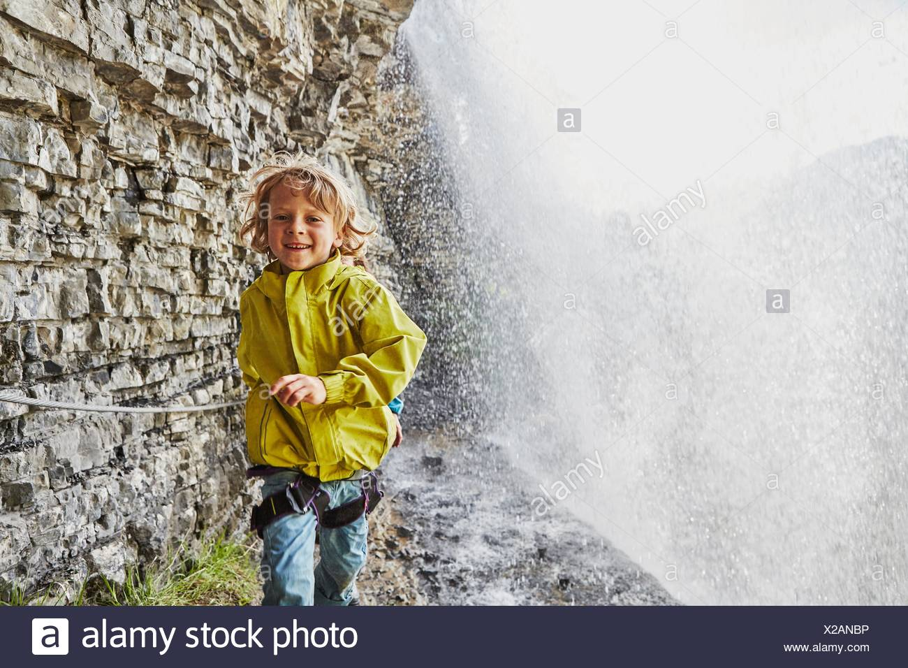 Young boy walking underneath waterfall, smiling - Stock Image