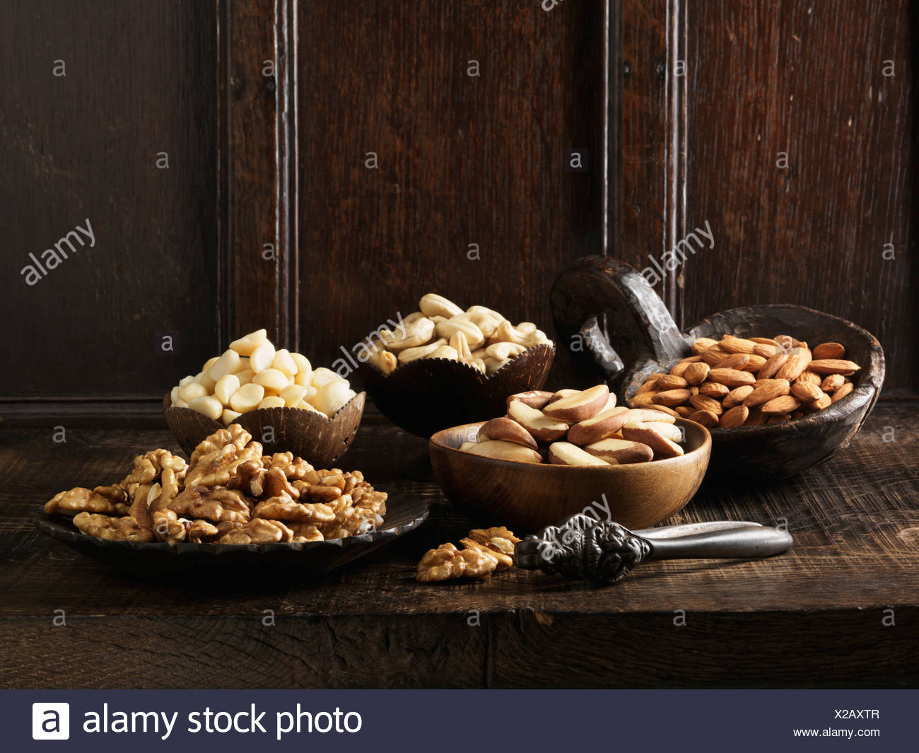 Nuts in assorted serving bowls - Stock Image