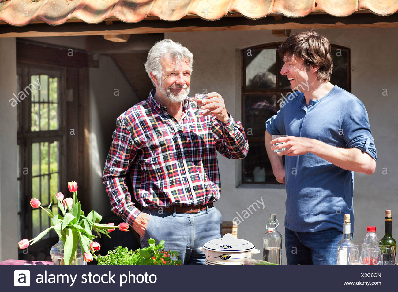 Father and adult son outside with drinks - Stock Image