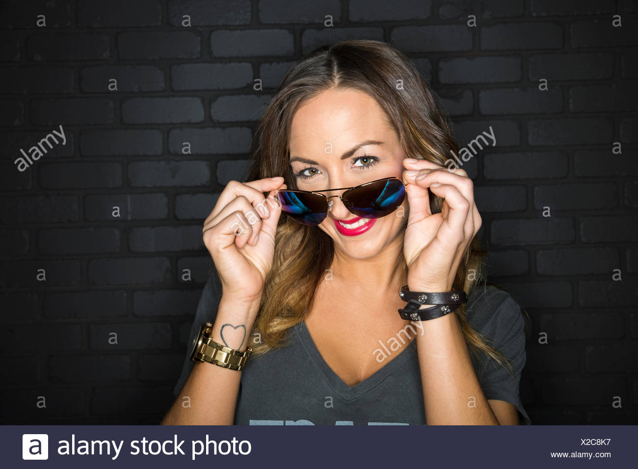 Portrait of flirtatious woman peering from behind sunglasses - Stock Image