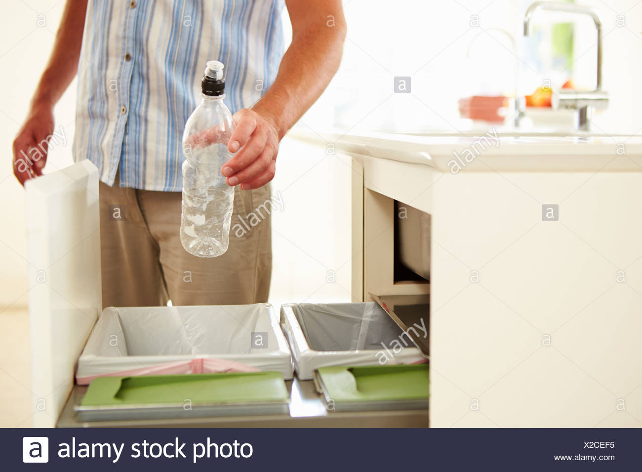 Close Up Of Man Recycling Kitchen Waste In Bin - Stock Image