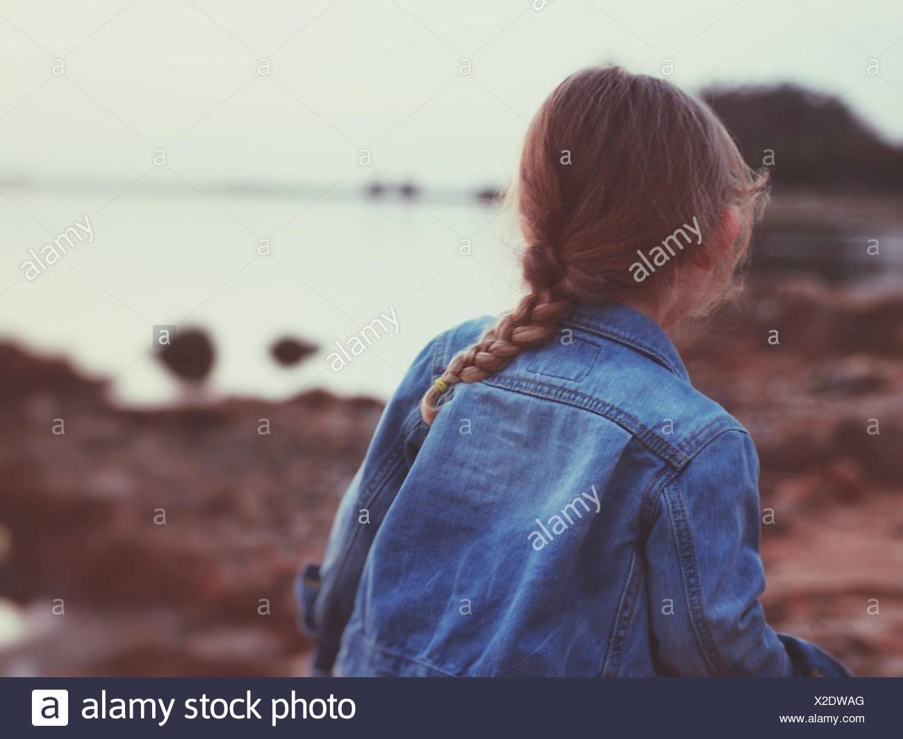 Rear View Of Girl Wearing Denim Jacket At Beach - Stock Image