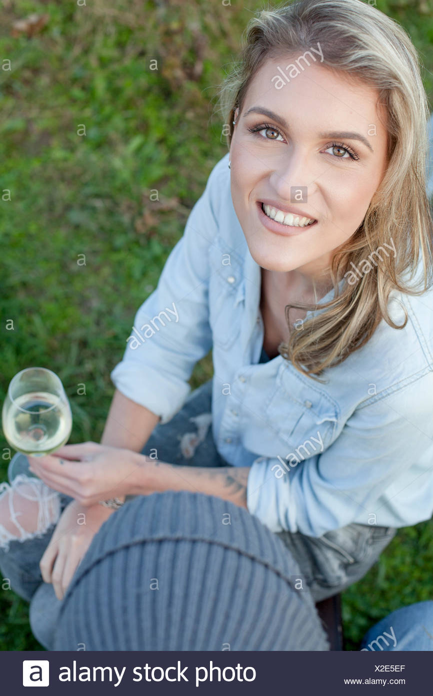 Woman with blond hair drinking wine on garden party - Stock Image