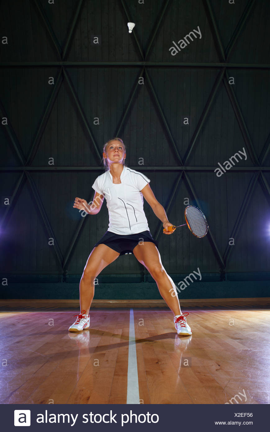 Young woman playing badminton on court - Stock Image