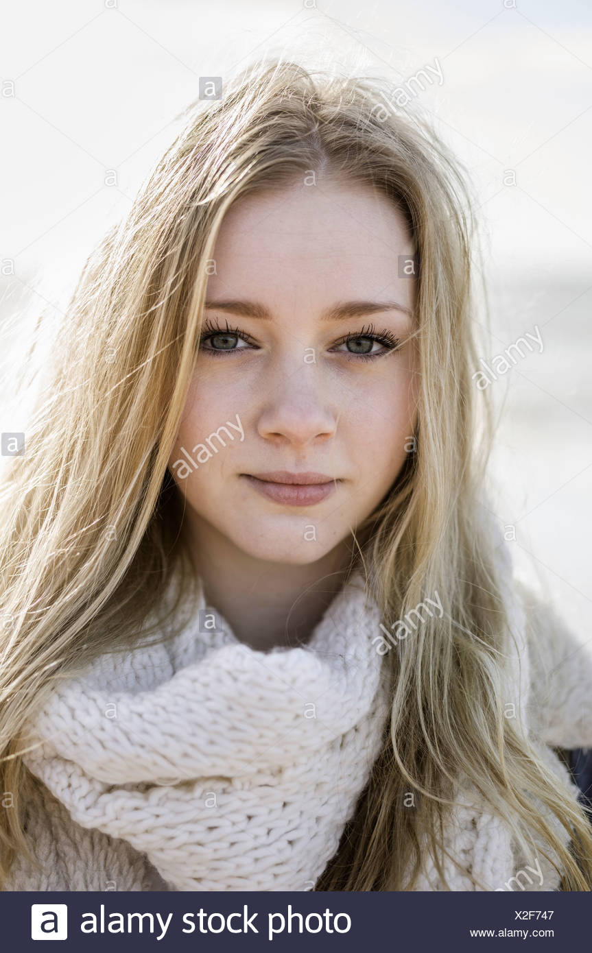 A young girl with blonde hair looking at the camera. - Stock Image