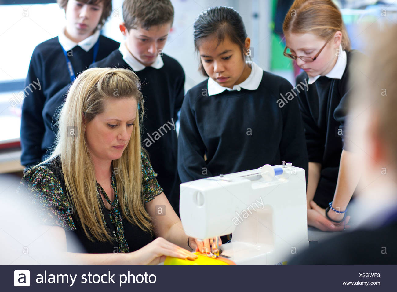 Students watch teacher use sewing machine in classroom - Stock Image