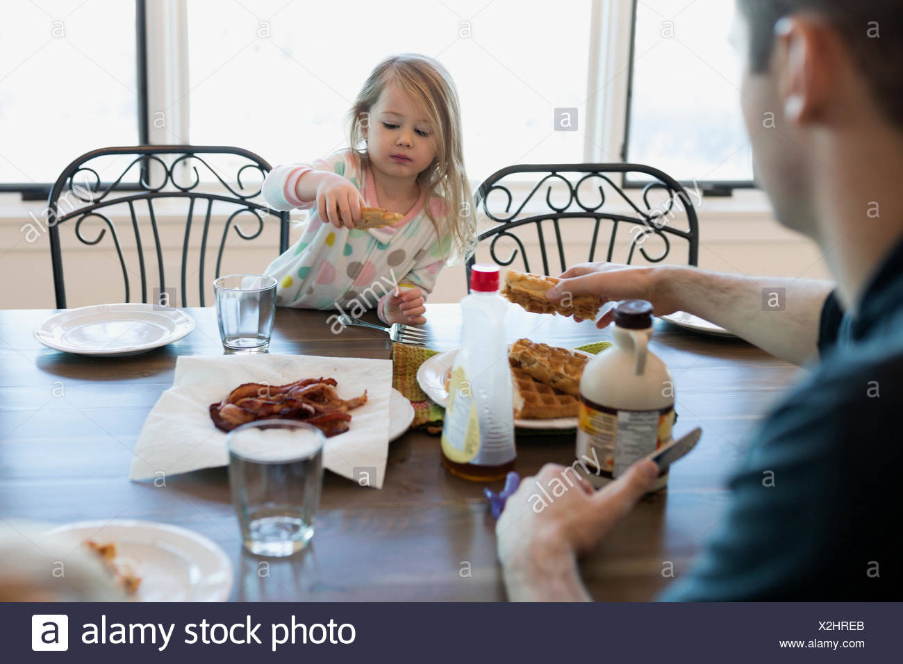 Father and daughter eating waffles at kitchen table - Stock Image