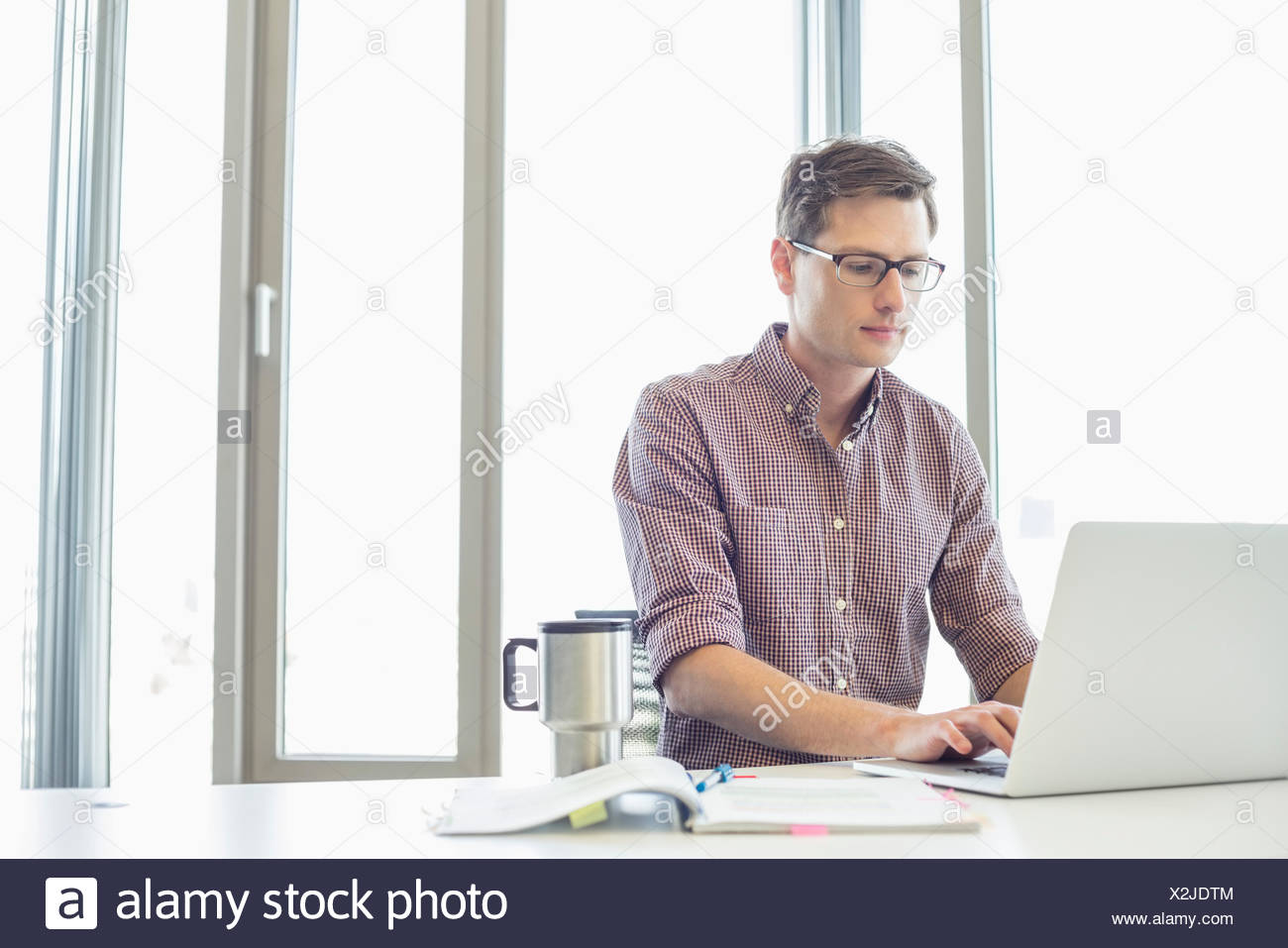 Businessman working on laptop at desk in creative office - Stock Image