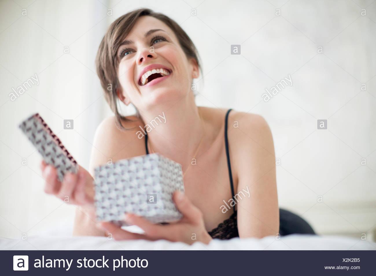Beautiful happy woman holding a gift box - Stock Image