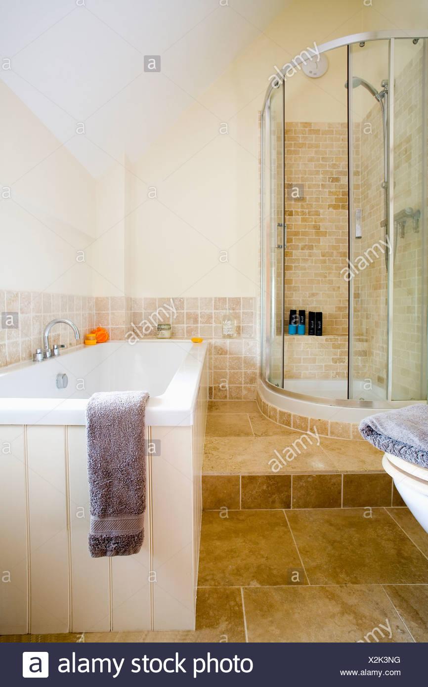 Corner shower with glass doors in split-level modern bathroom with ...