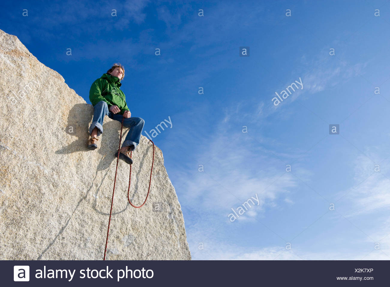 Climber sitting on peak - Stock Image