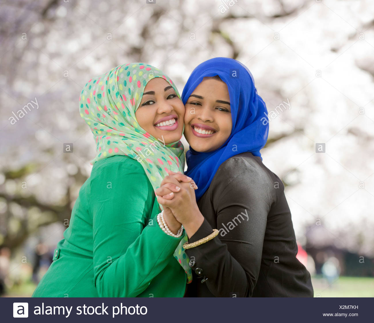 Portrait of two young females in park dancing together - Stock Image