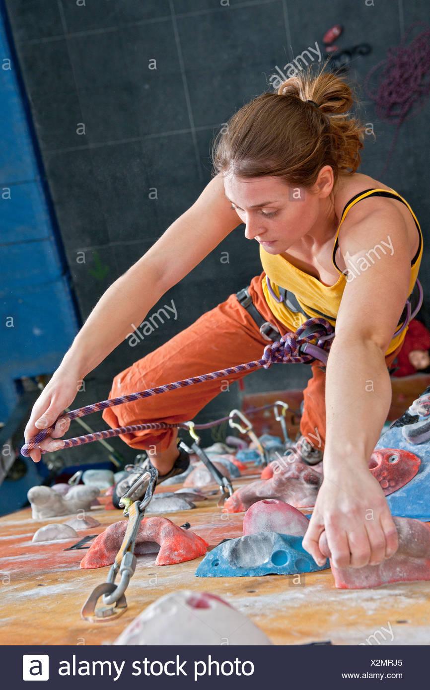 Woman climbing indoor rock wall - Stock Image