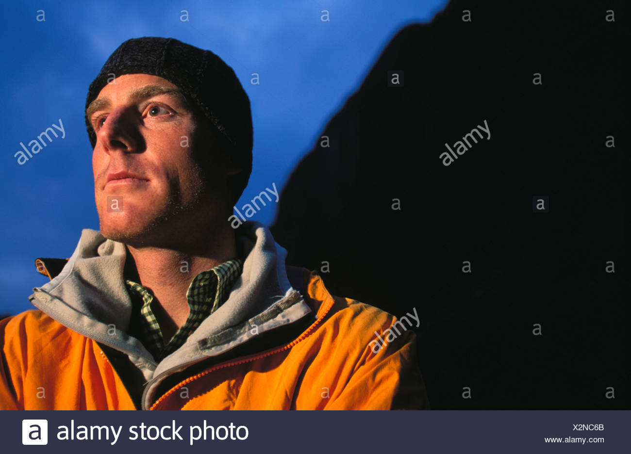 Lit headshot / portrait of a male climber, mountaineer, snowboarder. - Stock Image