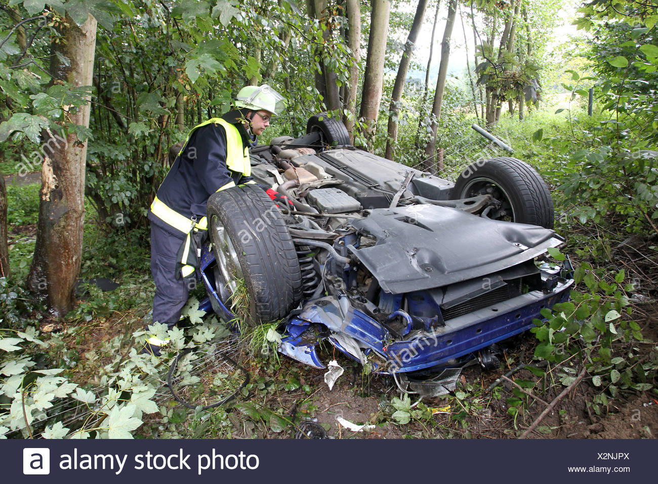 Firefighter attending a car wreck after an accident on the A48 Autobahn, motorway, Hoehr-Grenzhausen, Rhineland-Palatinate - Stock Image