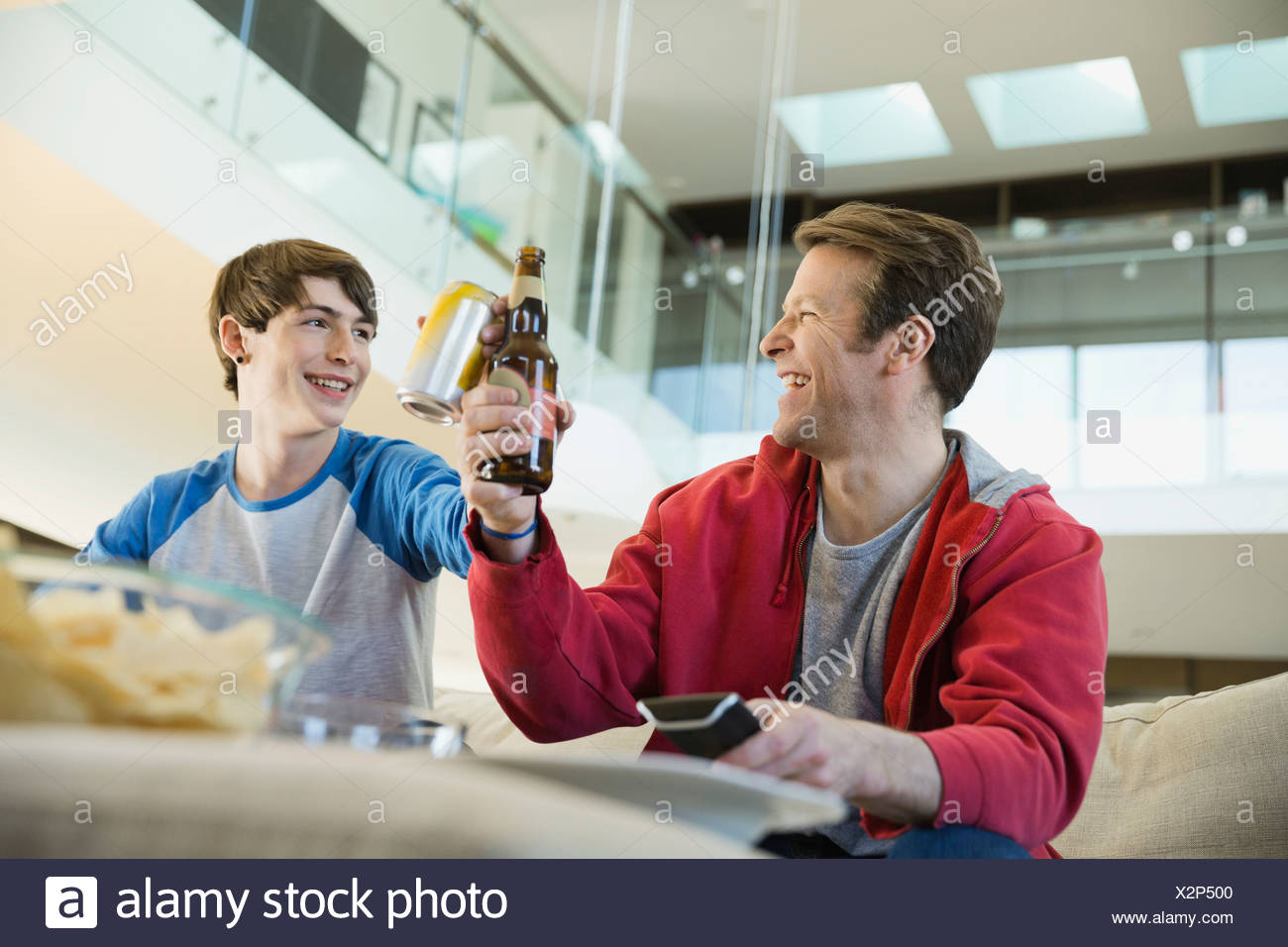 Father and son toasting drinks in living room - Stock Image
