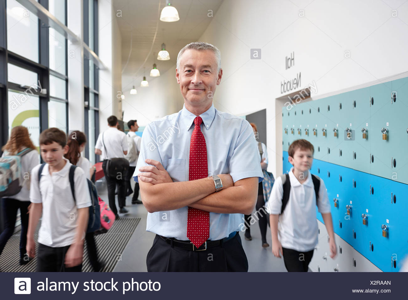 Portrait of male teacher with arms folded in school corridor - Stock Image