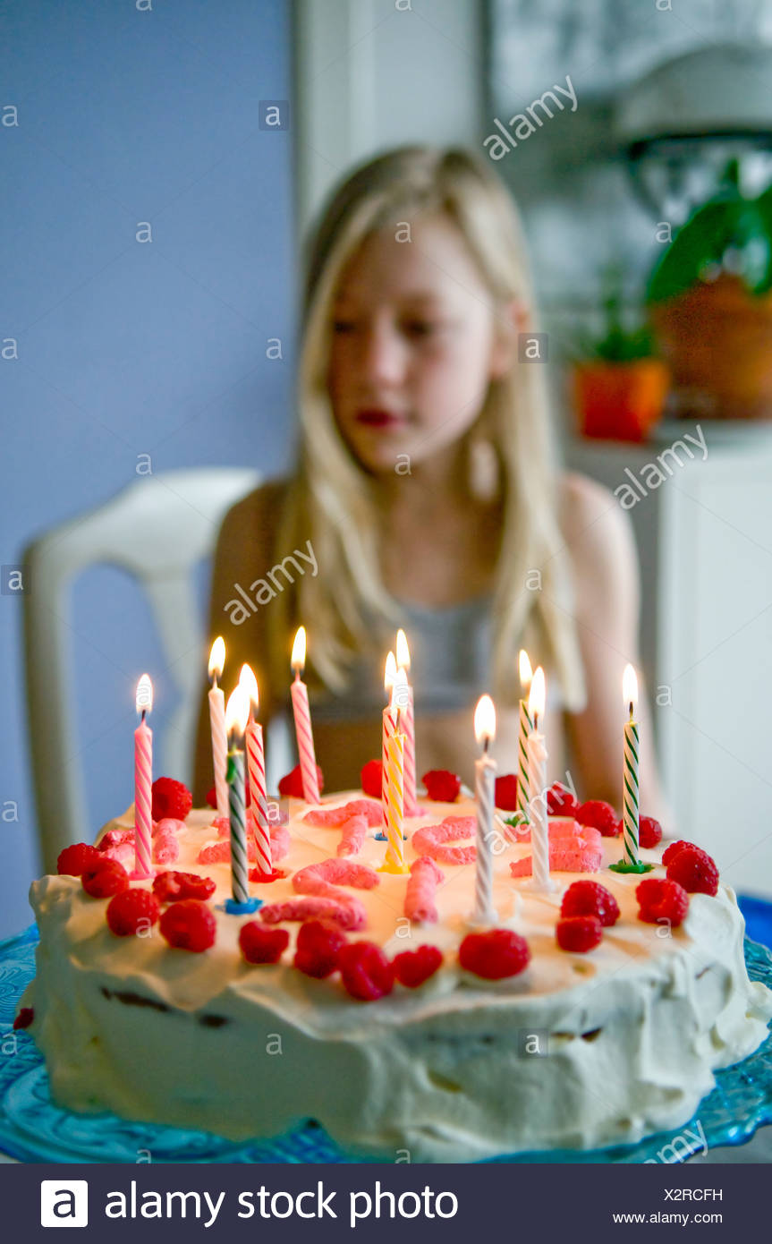 Lit Candles On Strawberry Birthday Cake With Blurred Blond Girl In