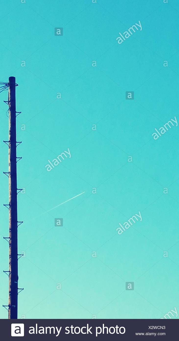 Pole Against Sky With Vapor Trail In Background - Stock Image